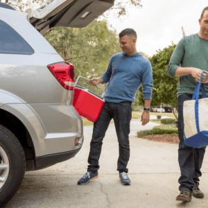 men taking bag and cooler out of car trunk