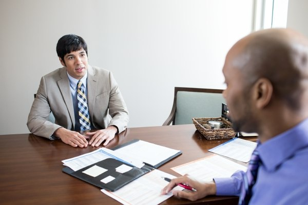 two men talking while sitting at a desk