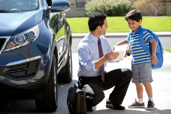 man kneeling to talk with his son beside car
