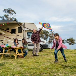 family playing and flying kite outside of rv