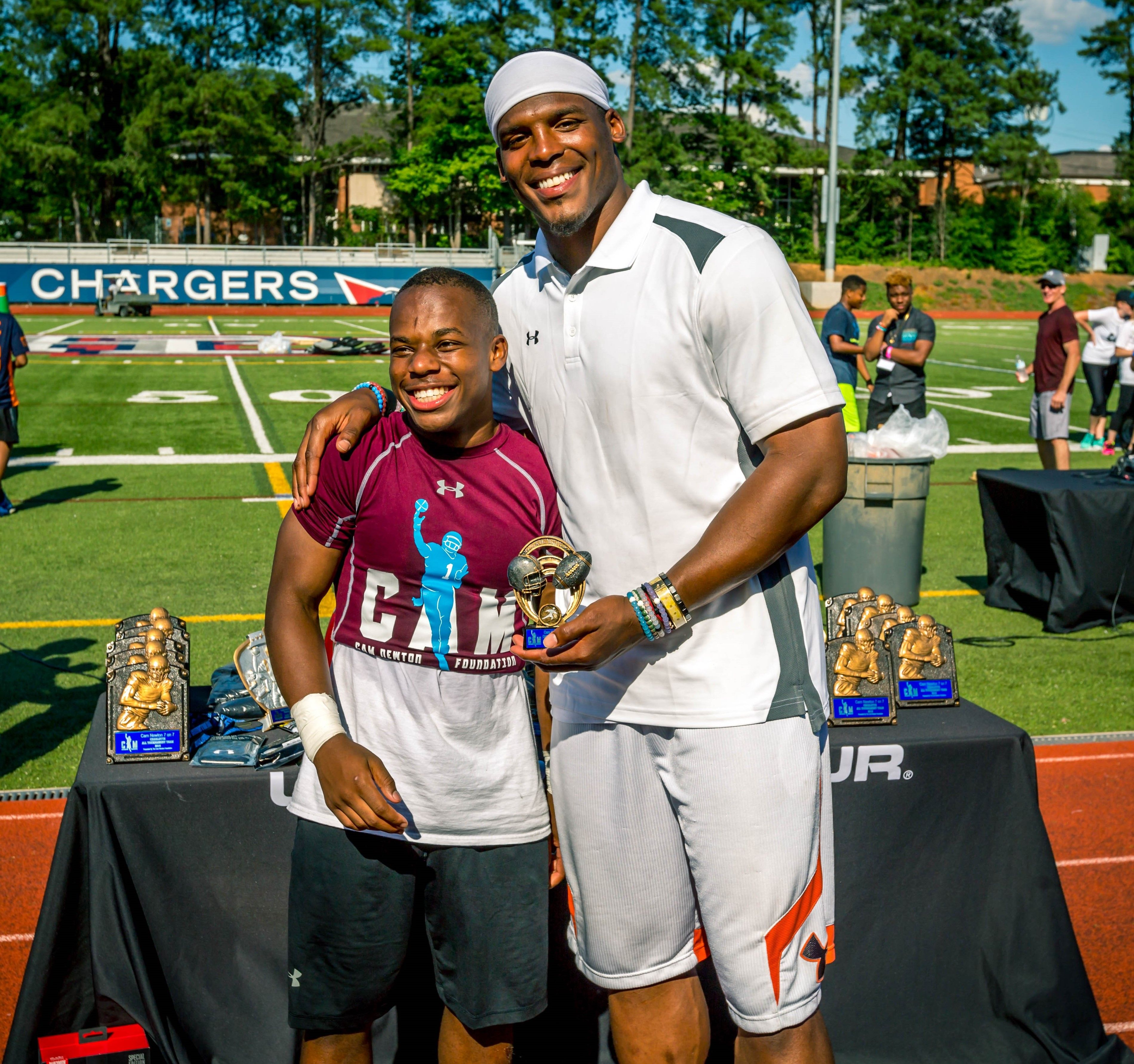 Cam Newton presenting a trophy to a child