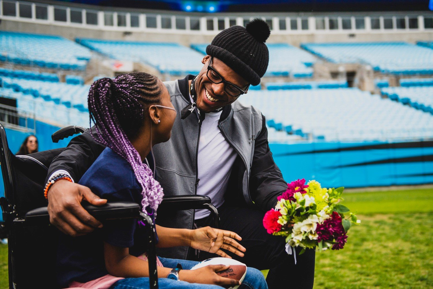 Cam Newton holding flowers and laughing with a girl with purple braids