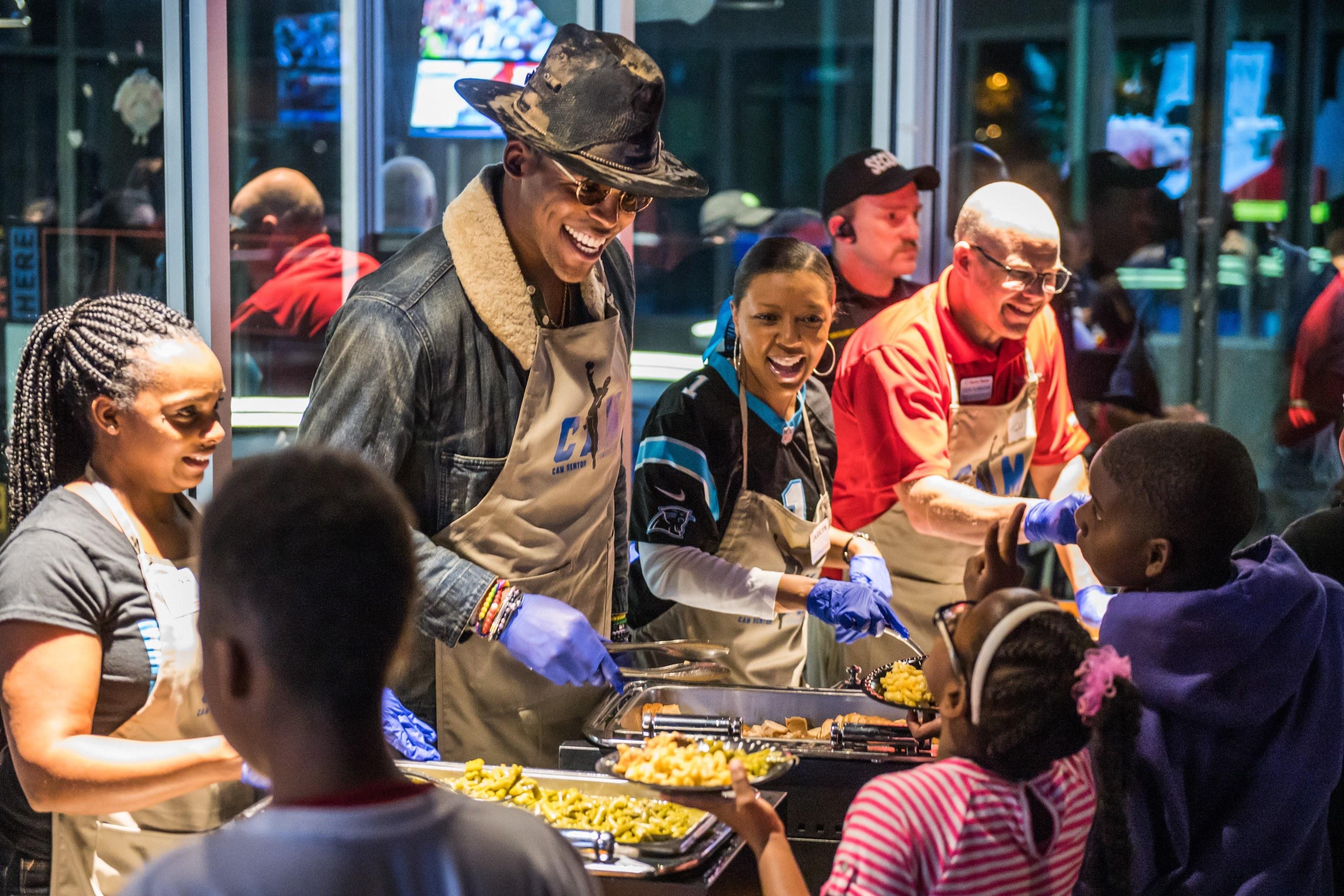 Cam Newton serving Thanksgiving dinner to children