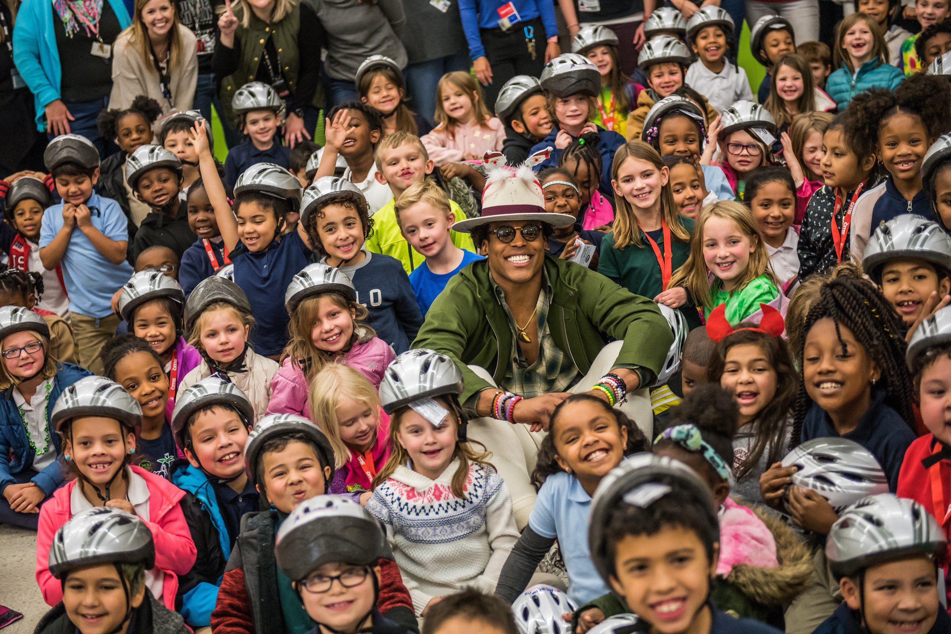 Cam Newton sitting with a large group of children