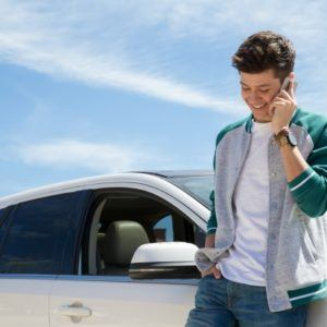 man on the phone next to a car