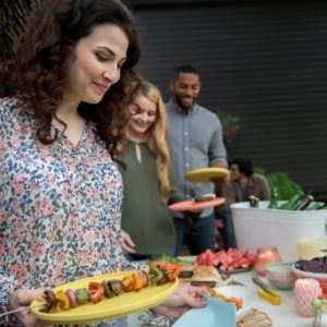people at a BBQ getting food