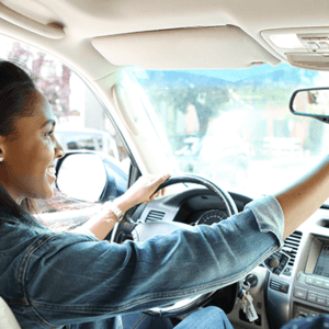 a woman checking the rear view mirror in her car