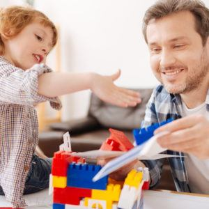 man and son playing with legos