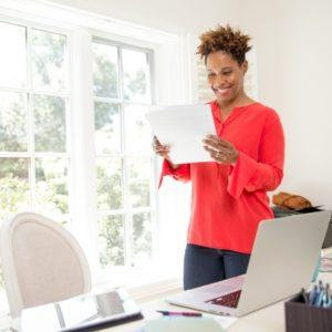 A woman reading paperwork in a home office