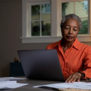 woman in orange shirt working on computer