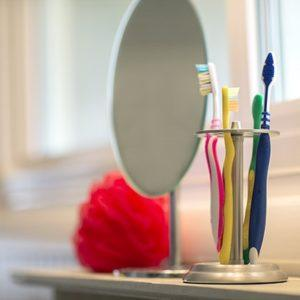 toothbrushes and a mirror in a bathroom