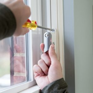 a person using a screwdriver on a window frame
