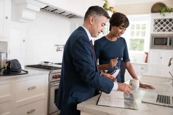 man and woman looking at documents at kitchen counter