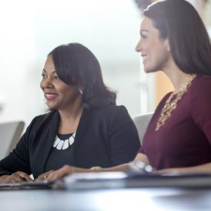 Two business women sitting at a conference table