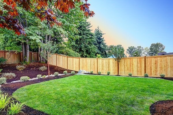 a nicely landscaped backyard with a new wooden fence