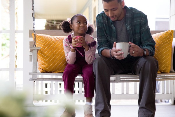 father and daughter on porch swing with coffee cups