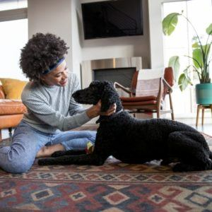 A woman sitting on the floor petting her dog