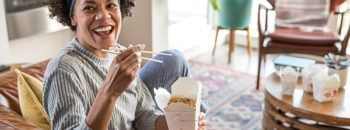 A woman eating Chinese food in her apartment