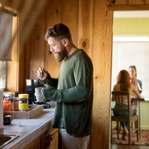 A man drinking coffee in the kitchen
