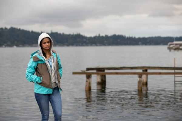 A person standing near a lake in rainy weather