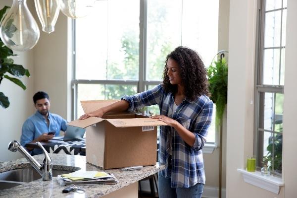 A woman opening a cardboard box