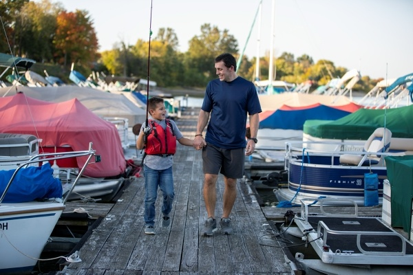 Father and son walking on a boating dock