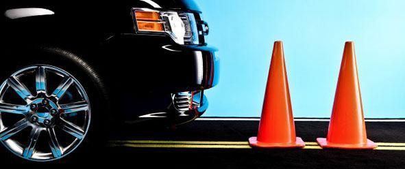 a black car in front of orange cones