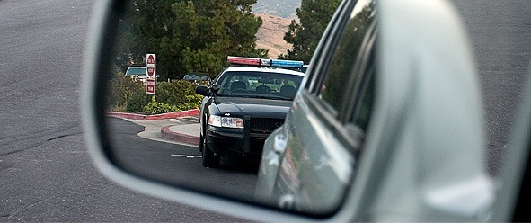 a cop car in a side view mirror of a car